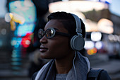 Confident young woman with headphones on urban street