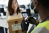 Woman receiving packages from courier with smartphone