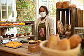 Confident female baker in face mask at pastry display