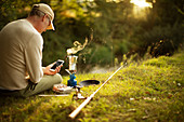 Man with smartphone taking a break from fishing making coffee