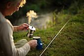 Man taking a break from fishing by making hot coffee