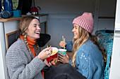 Happy women friends eating instant noodles in camper van