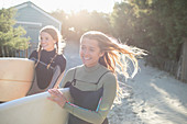 Happy female surfers with surfboards on sunny beach path