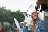 Happy woman eating instant noodles in camper van doorway