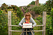 Smiling woman with crate of harvested apples in garden