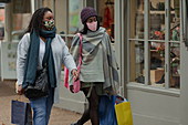 Mother and daughter in face masks with shopping bags