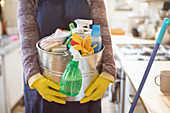 Woman holding bucket of cleaning supplies in kitchen