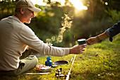 Couple camping and fishing making coffee at riverbank