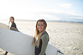 Happy young female surfer with surfboard on sunny beach
