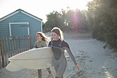 Young female surfers walking with surfboards on beach path