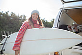 Carefree young female surfer with surfboard outside van