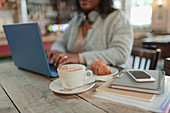 Woman using laptop next to croissant and cappuccino in cafe