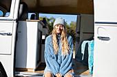 Young blonde woman in sunny camper van doorway