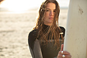 Young female surfer in wet suit on sunny beach