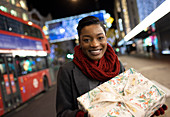 Young woman with Christmas gift on city sidewalk at night