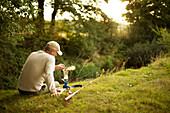 Man taking a break from fishing making coffee on riverbank