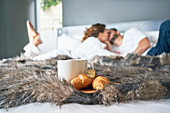 Couple kissing on bed behind croissant and coffee cup