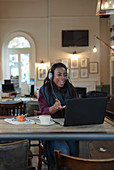 Businesswoman with headphones video conferencing at laptop