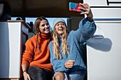 Happy young friends taking selfie in camper van doorway