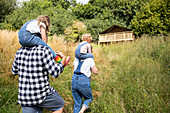 Parents carrying daughters on shoulders near cabin in woods