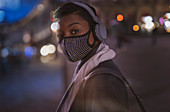 Young woman in facemask with headphones on street at night