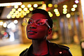 Young woman in funky glasses in city at night
