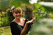 Smiling woman harvesting raspberries in sunny garden