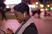 Young woman with headphones using phone in city at night