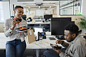 Happy business people eating takeout lunch at desk in office