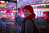 Young woman in red hat and scarf on city street