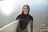 Happy female surfer in wet suit with surfboard on beach