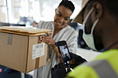 Courier in facemask with smartphone scanning package