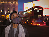Young woman in face mask with headphones on street at night