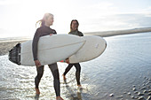 Young female surfers wading in sunny with surfboards