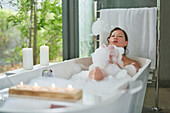 Playful woman in bubble bath in modern soaking tub
