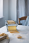 Rolling out pasta dough with a pasta machine