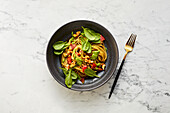 Pepper spaghetti with walnut pesto and spinach leaves