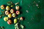 Apples and pears with leaves on a green surface