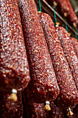 Salamis hang in a ripening room