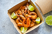Fried shrimps with lime slices in the fast food delivery box