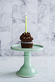 Geburtstags-Schokoladen-Cupcake mit einer brennenden Kerze