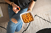 Woman's hand holds bowl of Cape gooseberries