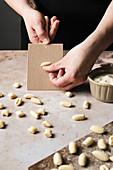 Hands rolling cavatelli pasta on a gnocchi board
