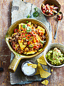 Nachos with mincemeat, cheese and two sauces