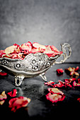 Dried rose petals in a silver sauce boat