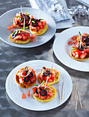 Corn canapes with tomato salsa and anchovies