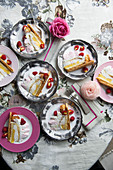 Cream cake with raspberries, cake pieces on plates