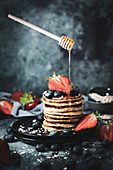 Healthy oat pancakes with berries and honey