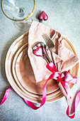 Christmas table setting with dust pink plates and cutlery in served setting for Christmas dinner