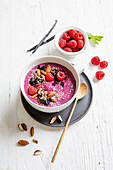 Pink smoothie bowl with raspberries and almonds